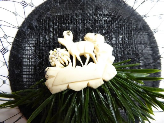 "Fascinator with vintage ""plastic"" brooch of chamois deer and pine green, black tulle on a black sinamay base with comb. €120"