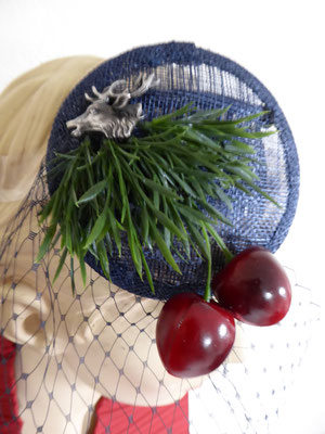 Blue sinamay base with black tulle, cherries and pine needles.....€59