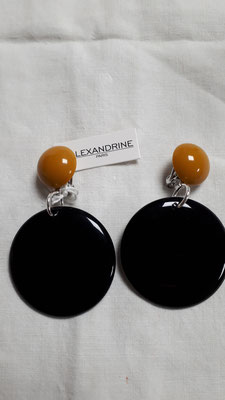Large black discs with maize boutons. €85
