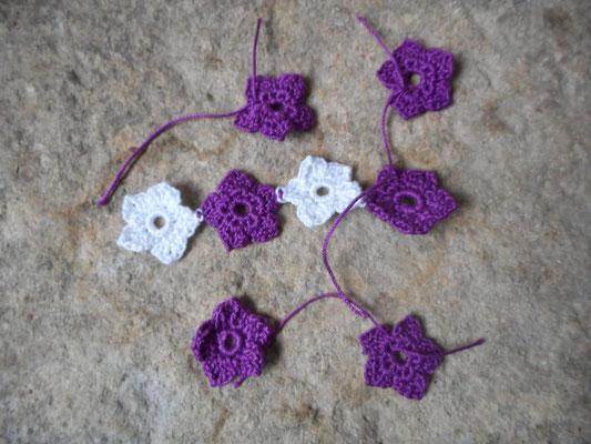 quleuqles petites fleurs de coton blanc et violet qui seront prochainement incluses dans un collier au crochet avec perles