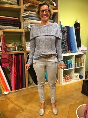Auch sie strahlt über den fertigen Pullover mit dem ausladenden Kragen.