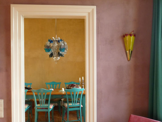 Blick auf den Kronleuchter in der Küche, farbig verputzte Wände im Werkhaus