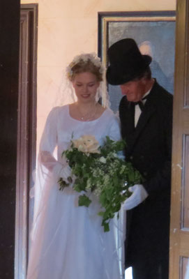 Der Brautvater geleitet seine Tochter in den weißen Saal, den Ort der Trauung.
