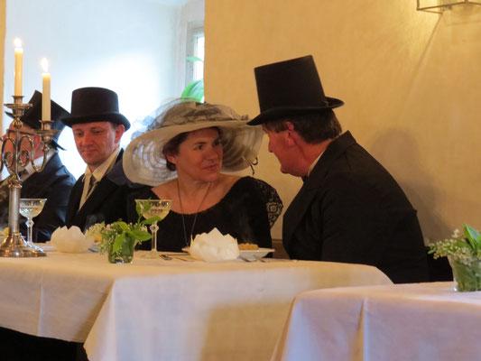 Die Brauteltern freuen sich über das Glück ihrer Tochter, von einem Trauzeugen beobachtet.