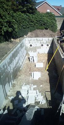 Teichbauer verfüllen Schalungssteine mit Beton und Torstahl