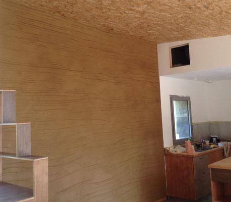 Enduit de finition terre texturé sur mur en paille