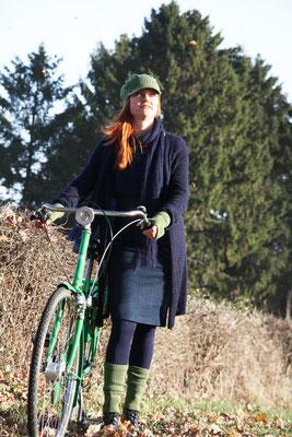 """Das Model trägt Mütze """"Antonia"""" und Fingerlinge """"Romy"""" in Merinowolle mittelgrün, Schal """"Mona"""" und Mantel """"Stella"""" in Mohair Seide dunkelblau"""