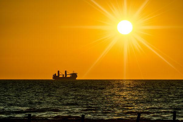 Warnemünde - Sonnenuntergang mit Schiff am Strand von Warnemünde