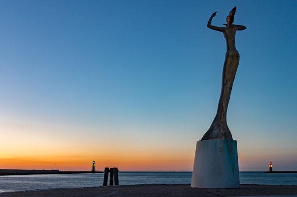 """Warnemünde - Statue """"Püppi"""" an der Mittelmole in Warnemünde begrüßt die Schiffe zur blauen Stunde"""