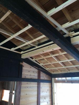 母屋補強部分は、古い丸太の下端に天井を差し込み、新しい添え梁を母屋に見せる。