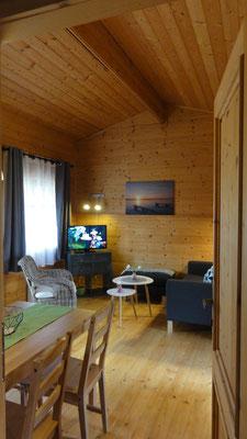 Wohnzimmer Typ A © Blockhäuser auf Naturcamping ZWEI SEEN / www.zweiseen.de/blockhaus