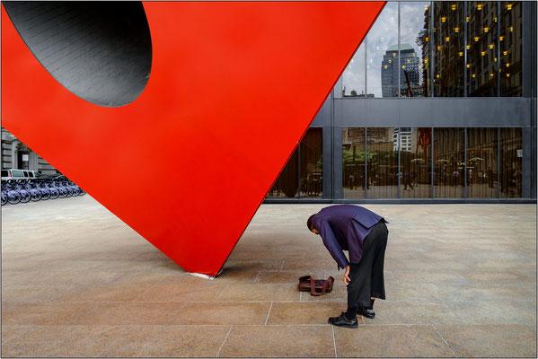 """New York City: musulmano in preghiera a Broadway dinanzi alla scultura """"Red Cube"""" di Isamu Naguchi - © Massimo Vespignani"""