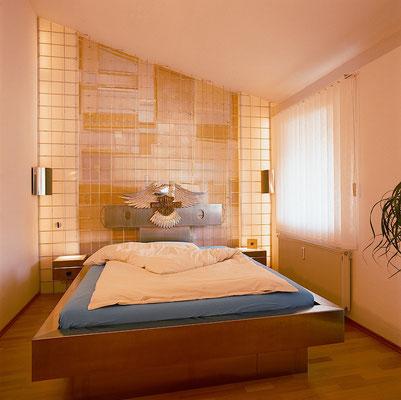 Bett mit hinterleuchteter Wandgestaltung
