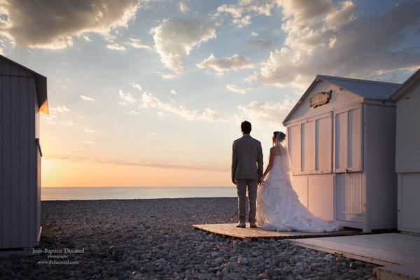 Photo de mariage coucher de soleil pres des cabines de plage