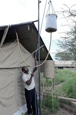 Die warme Dusche wird vorbereitet – Kati Kati Camp