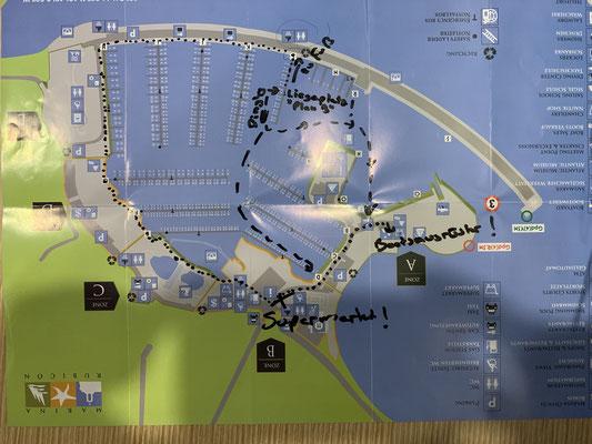 Hier der Lageplan der Marina ... ich liege am Steg L in der Mitte ... zum Bootsausrüster und Supermarkt müsste ich ganz außen um den Hafen herumgehen (siehe gepunktete Linie) ... mit dem Boot kann ich einfach quer rüber!
