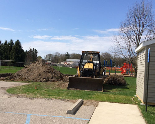 Mid-April: Back lawn at the schoolhouse with piles of dirt and stacks of roots