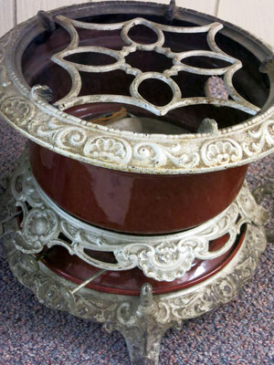 This rare iron kerosene burner features three wicks and very ornate metal trim. The burner was brought to America when Dick and Jessie Valk emigrated from the Netherlands.