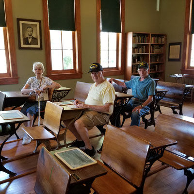 Relaxing at a school desk in the 1881 two-room schoolhouse (photo by Debbie)