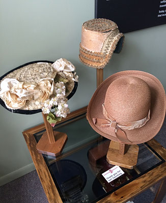 The hat display shows a variety of summer hats.