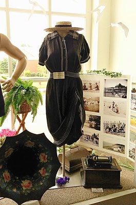 The 1920s lady's bathing suit features a blouse and attached bloomers with a button-down skirt.