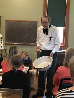 The schoolmaster asks a student if she needs to wash her hands.