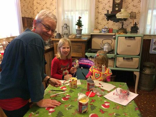 Volunteer Linda Kolk helps the children make a cocoa stirrer. ::photo by Susan Norder