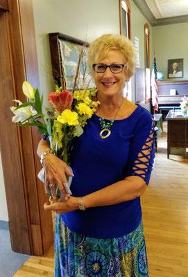 Elaine takes home a floral bouquet.