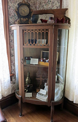 Antique curio cabinet was hand crafted in an oak finish. Notice the beveled mirror back splash, delicate wood trim on the center door and the convex glass side panels.