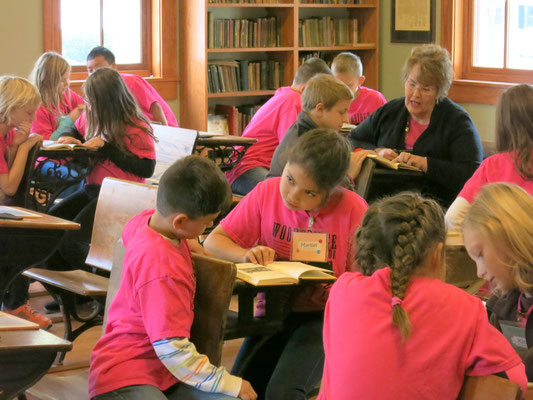 The children share a textbook