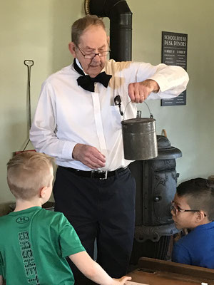 """Holding a lunch bucket, Schoolmaster Boehm asks, """"What is the purpose of this artifact""""?"""
