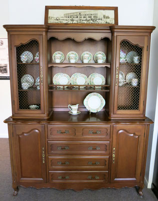China cabinet (c. 1950s) made by Colonial Manufacturing Company with a panoramic photo of Colonial Manufacturing Company employees (c. 1926)