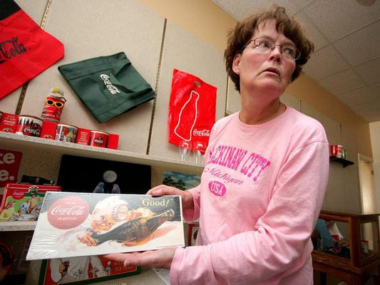 Kathy Westveld holds a Coca-Cola sign currently on display inside the Zeeland Historical Society. Rob Wetterholt Jr./Sentinel Staff