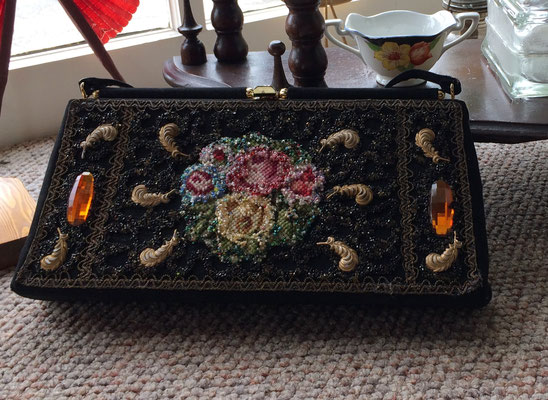 This lovely purse is decorated with 10 metal feathers, 2 amber-colored jewels and a centered tapestry