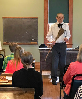 Schoolmaster Boehm holds an antique corn broom looking for a student to sweep the floor.