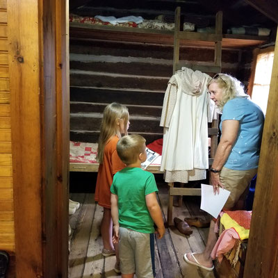 Visiting the log cabin to see how the pioneers dressed