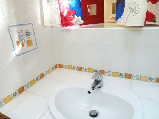 La salle de bain du gîte est lumineuse grâce à sa petite fenêtre au dessus du lavabo et sa fenêtre de toit.