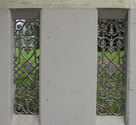 Pluwig, Kirchplatz. Moderne Beton-Balustrade zum Pfarrgarten mit moderner filigraner Gußeisenornamentik.