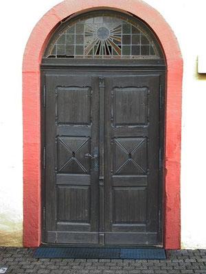 Seiteneingang. Kassettentür. Darüber Kreisbogenfenster mit Sonnenmotiv mit Stern. Gewand aus rotem Sandstein.