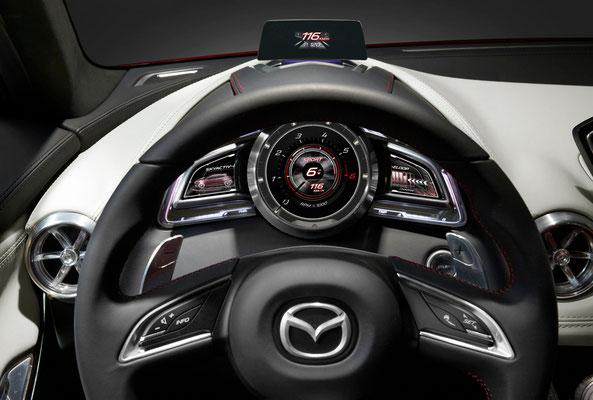 マツダ跳(HAZUMI)インテリア メータークラスターは、中央に配置した一眼ゲージを、ウイング状のディスプレイが左右から挟み込むことで、ドライバーの中心軸を意識したデザインとしました。センターディスプレイ、アクティブドライビングディスプレイ、コマンダーコントロールは、「Heads-Up Cockpit(ヘッズアップコクピット)」コンセプトに基づき、多くの情報を扱いながらも、正しい姿勢で安全に 運転に集中できる配置としています。(公式資料より)