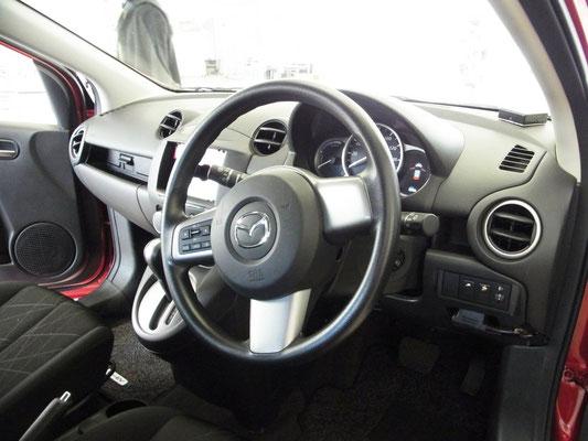 デミオEV レンジエクステンダーの運転席。一見通常のデミオと変わりませんが、オーディオ部分の「エマージェンシーボタン(!)」等所々に違いが。