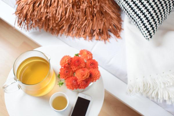 Gemütliche Stunden im Bett mit Tee, weichen Kissen und frischen Blumen.