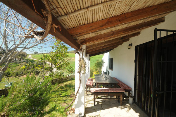 Die überdachte Terrasse mit großem Esstisch, für Frühstück wie Abendessen gleichermaßen schön