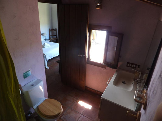 Das Badezimmer mit Schlafzimmer im Hintergrund.