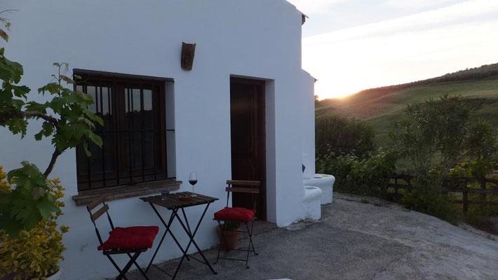 Bei einem Glas Wein den Sonnenuntergang genießen