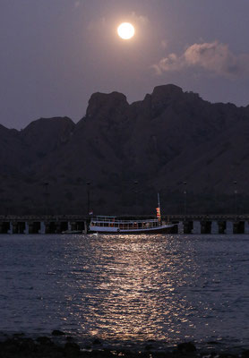 Full moon above the bay of Komodo with our boat at the pier. © Jasper Boldingh