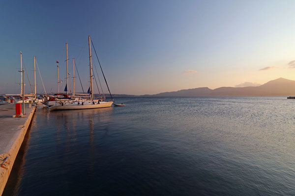 The sun sets in the harbour of Adamas.