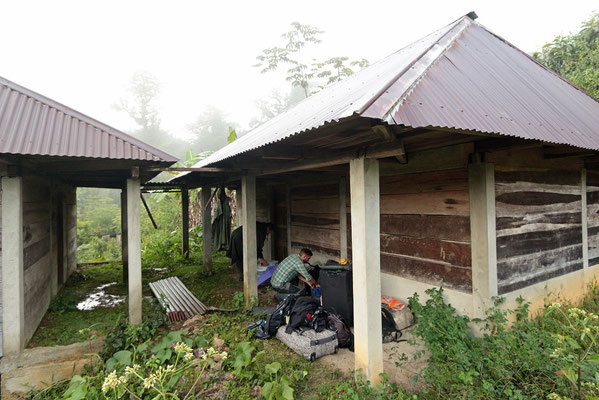 Stalling our luggage under the roof of this abandoned house during a downpour.