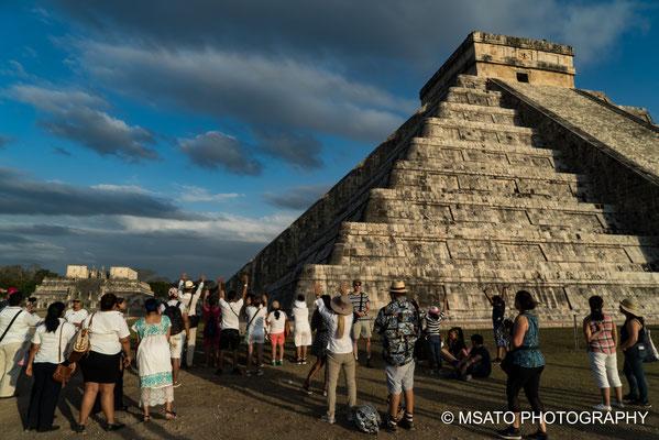 Quando o sol se põe, turistas de todo mundo erguem as mãos louvando a vinda da Serpente Emplumada.