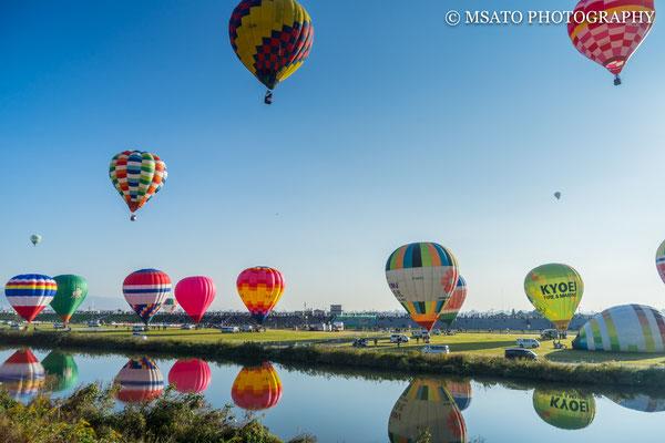 41 - Província de SAGA. 41 - Província de Festival de balões de Saga. Os balões de ar quente não são equipados com volante ou guidão para guiá-los. Os pilotos aquecem o ar ou os extraem para subir ou descer. O deslocamento lateral fica por conta do vento.